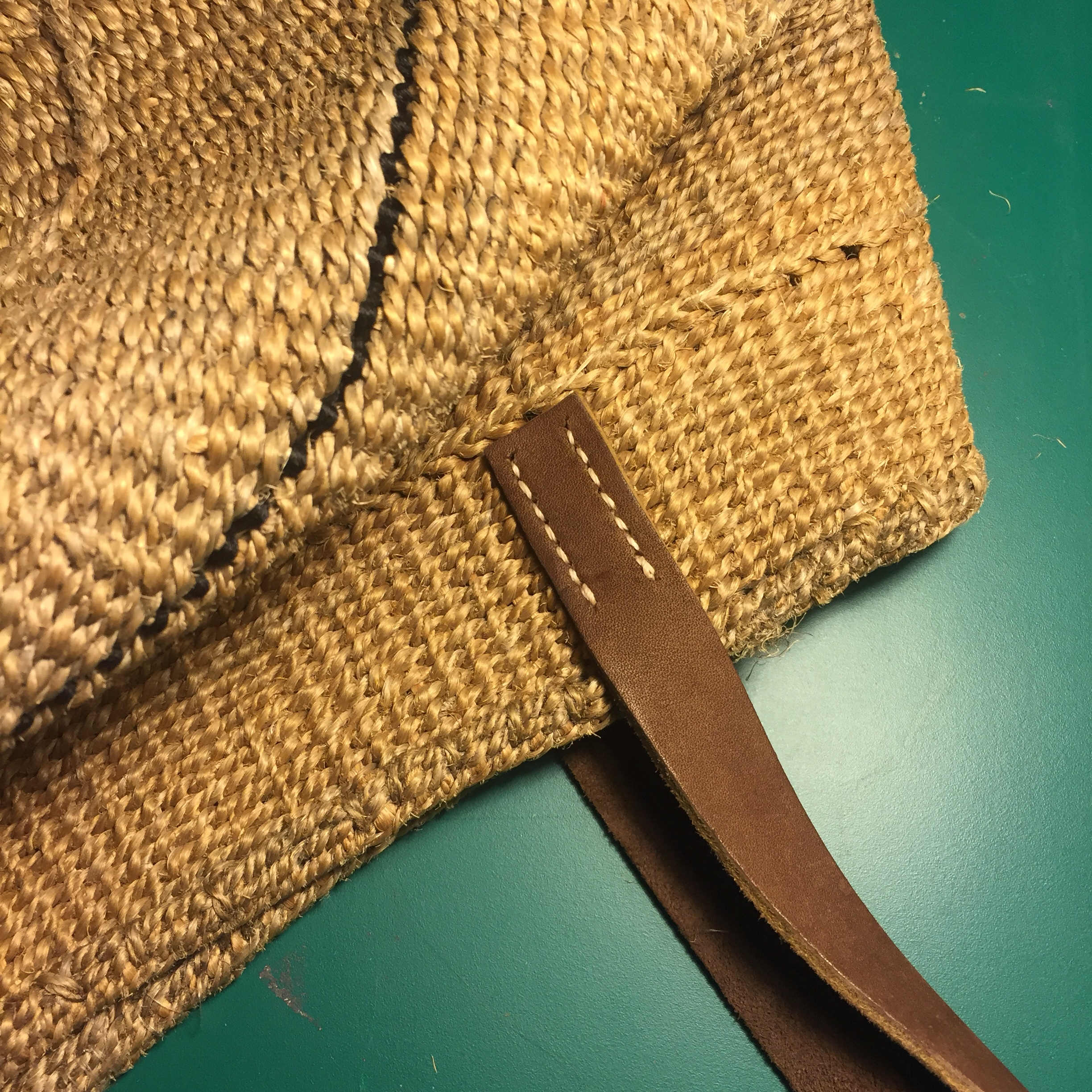 Brown leather strap repair on straw bag