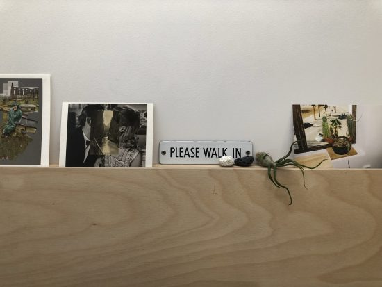 Postcards, rocks and an airplant arranged on a picture rail