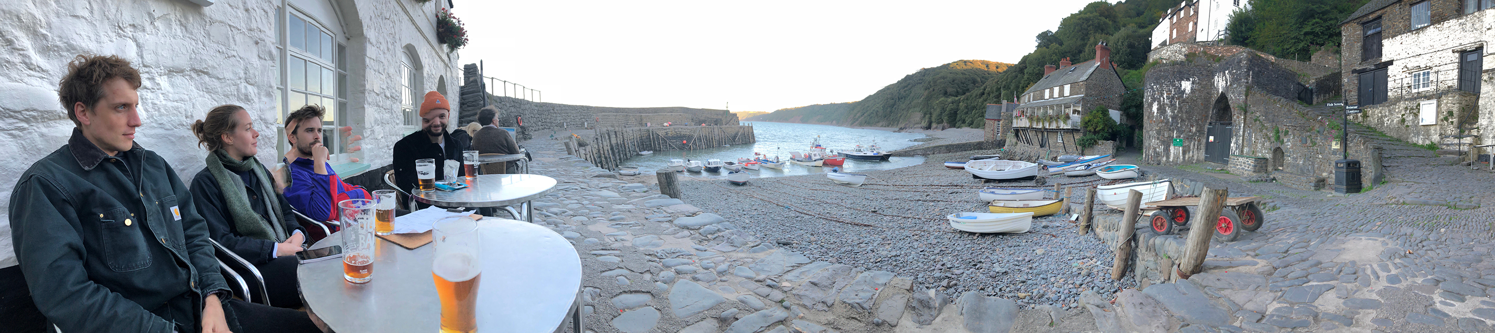 Panoramic photo of friends with pints in Clovelly Bay, Devon