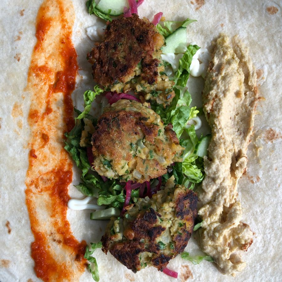 Falafel wrap with chili sauce, lettuce, cucumber, pickled onion, and hummus