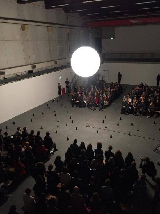 A glowing orb suspended over an audience and an assortment of metronomes in a darkened room