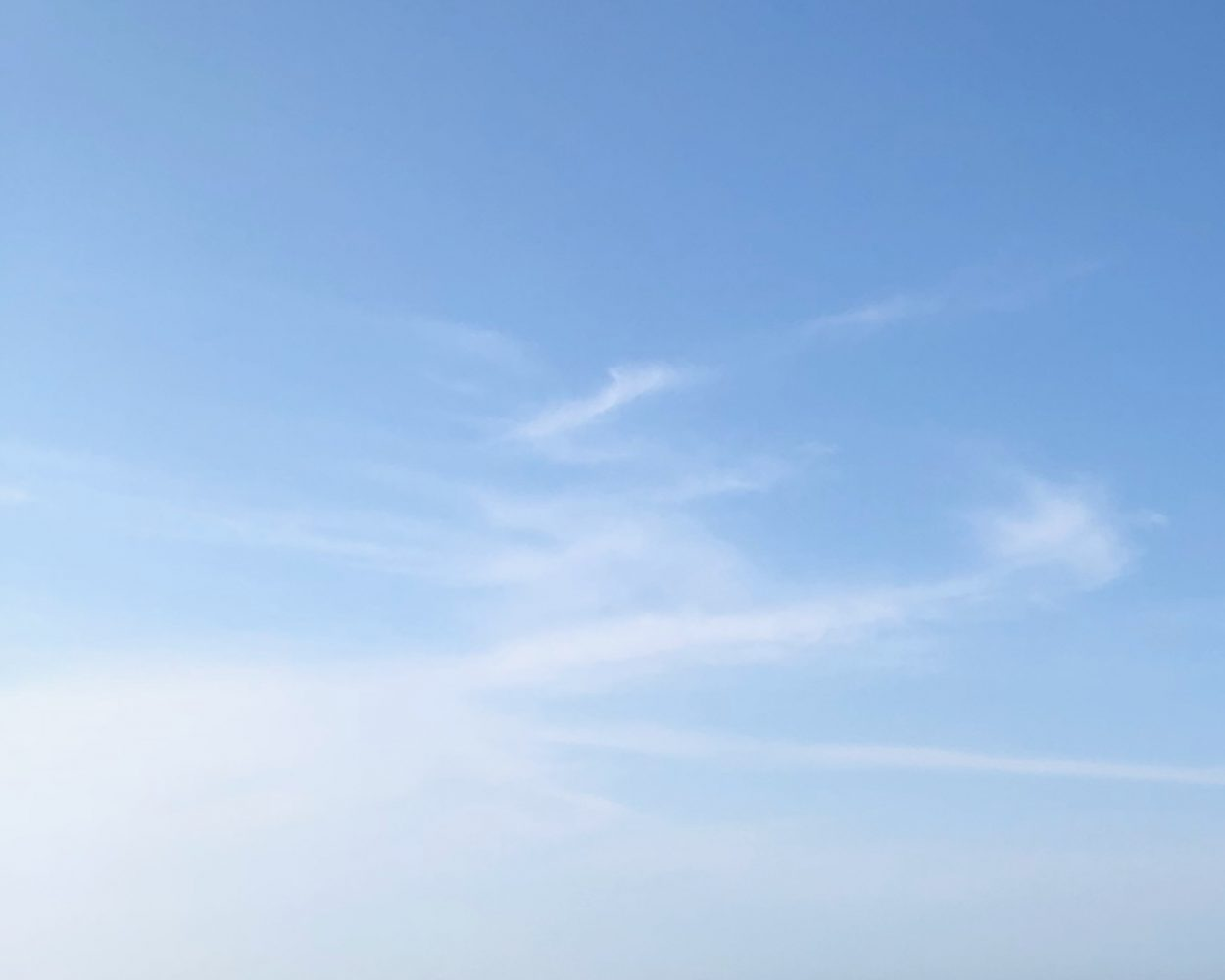 Cirrostratus clouds against a pale blue sky