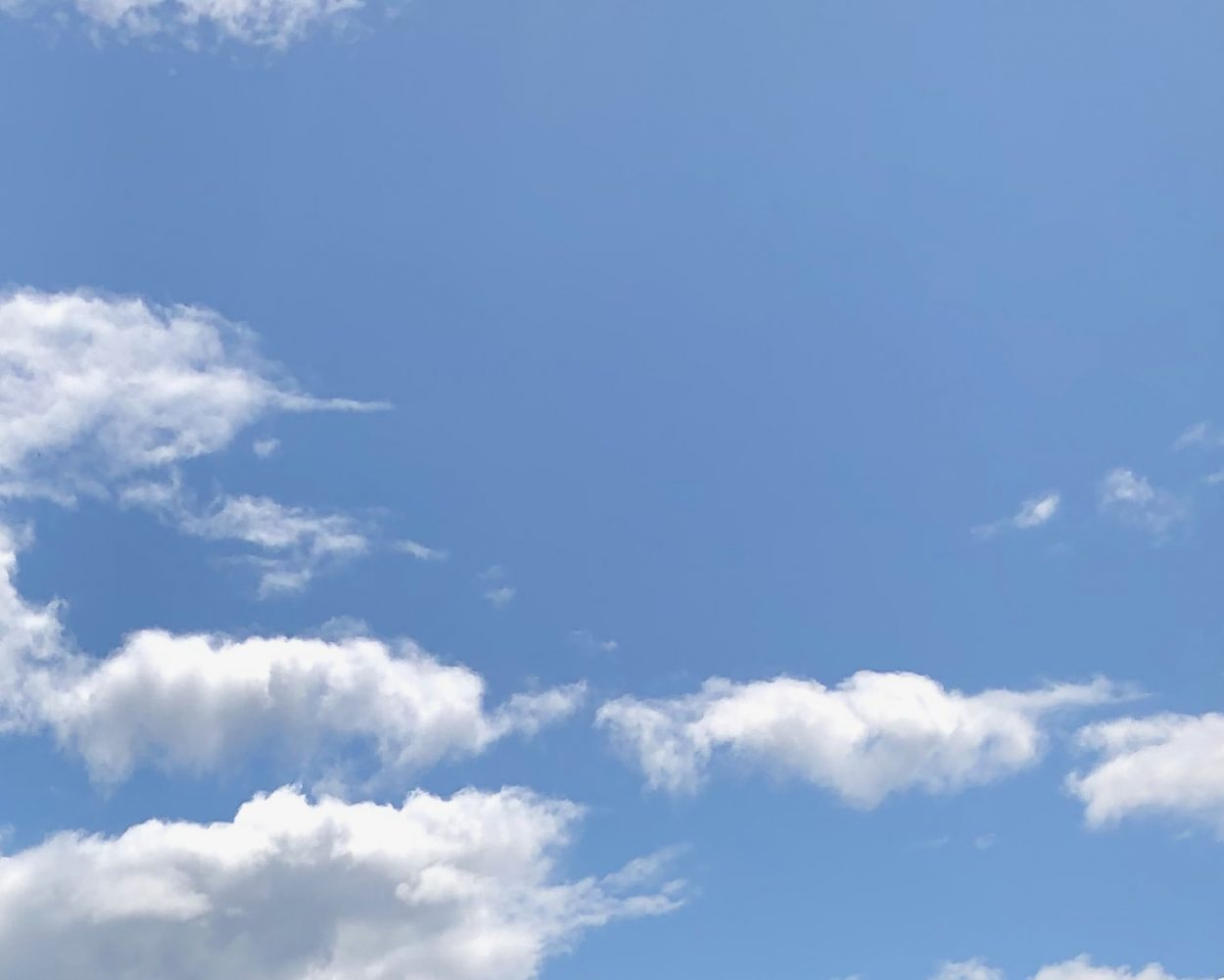 Cumulus clouds against a pale blue sky
