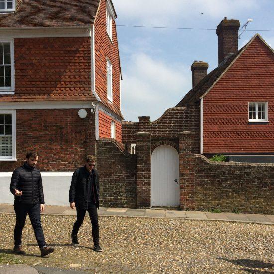 Two guys walking past brick houses in Rye