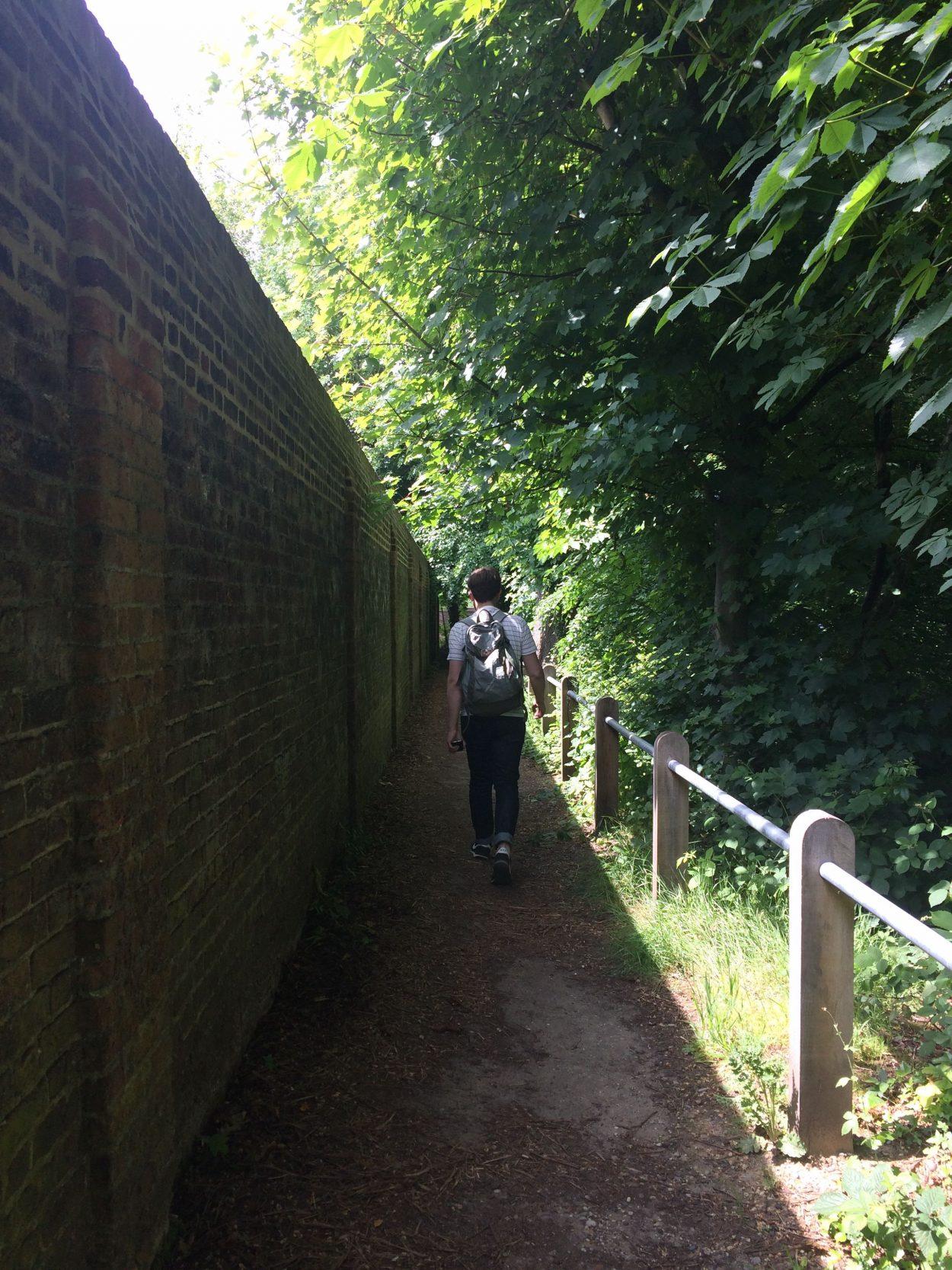 A man walking half in shade half in sun