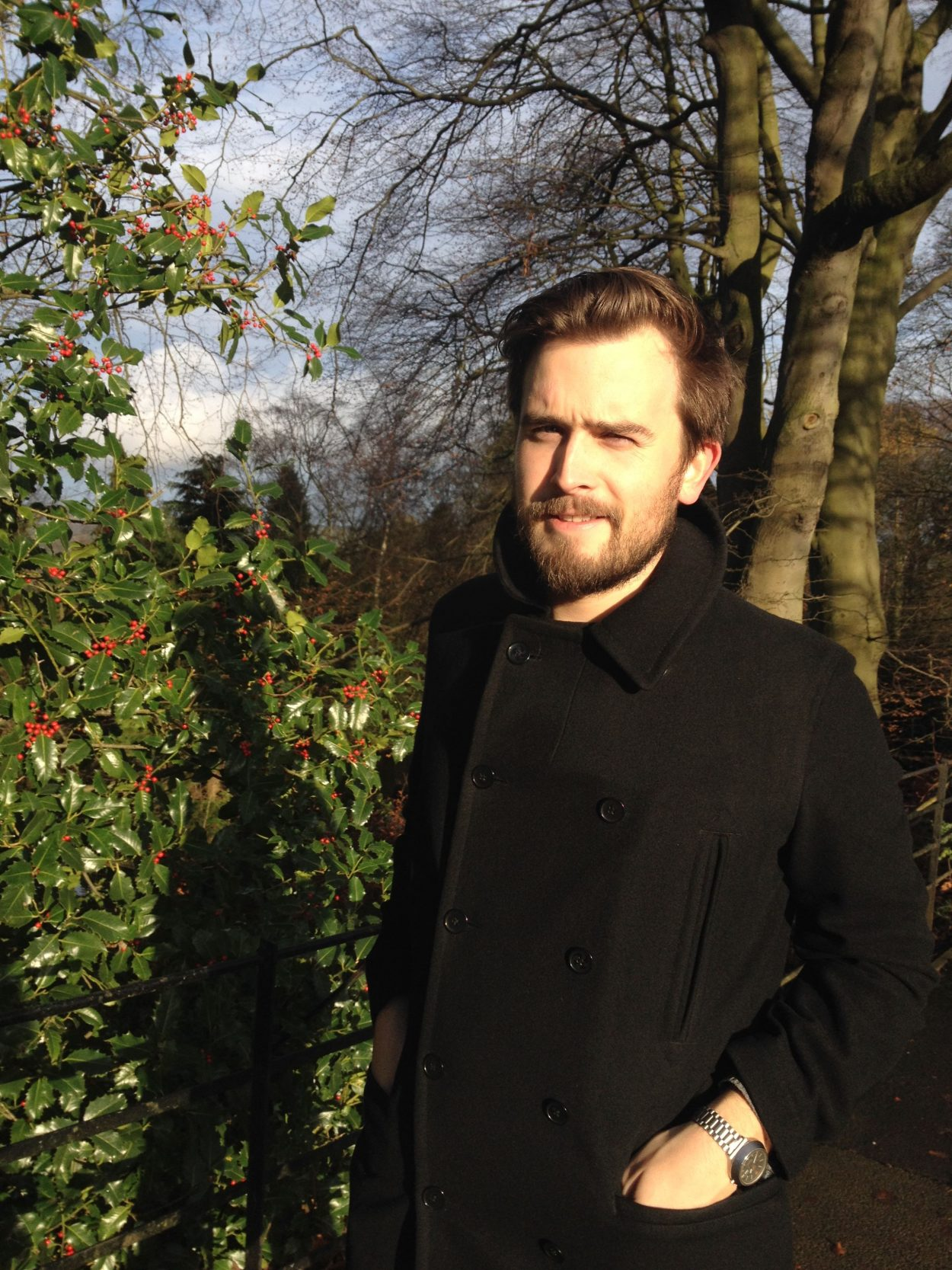 A man in a black pea coat standing in front of holly bushes as the sun sets