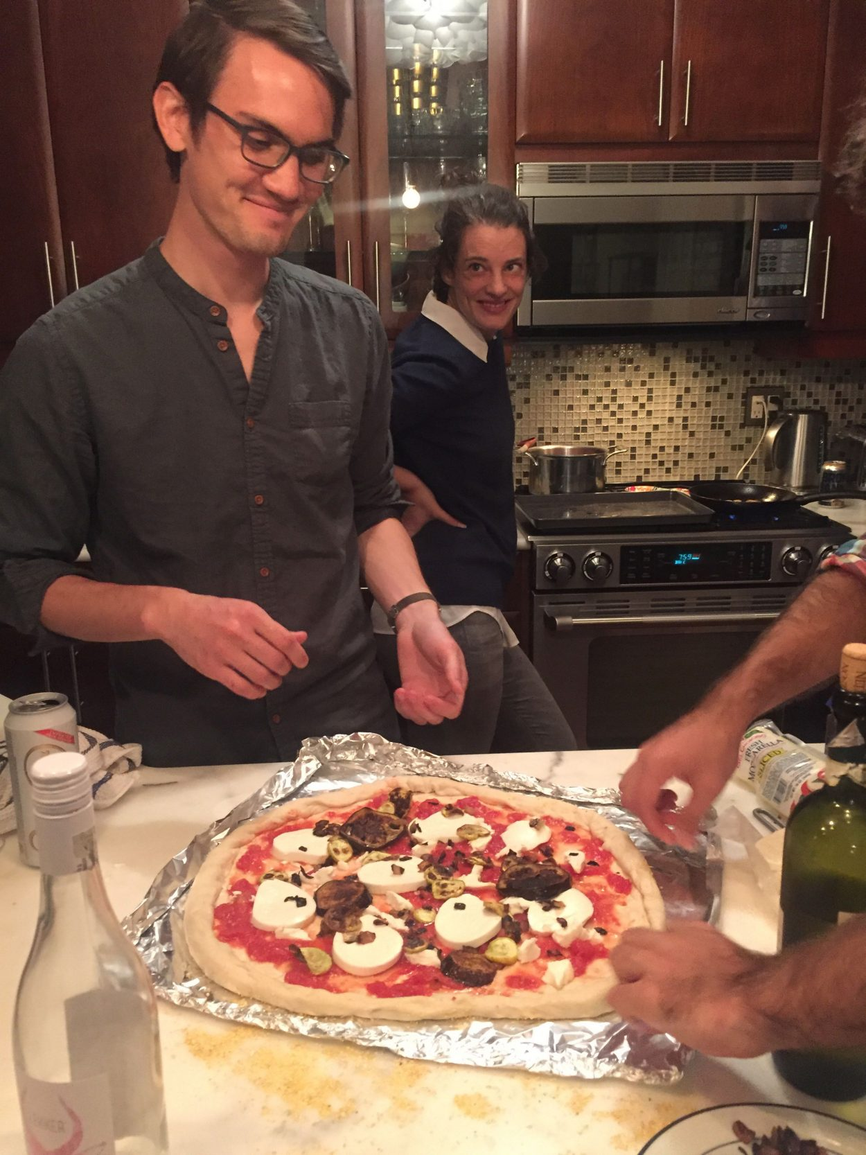 Photo of two people making pizza in a home kitchen