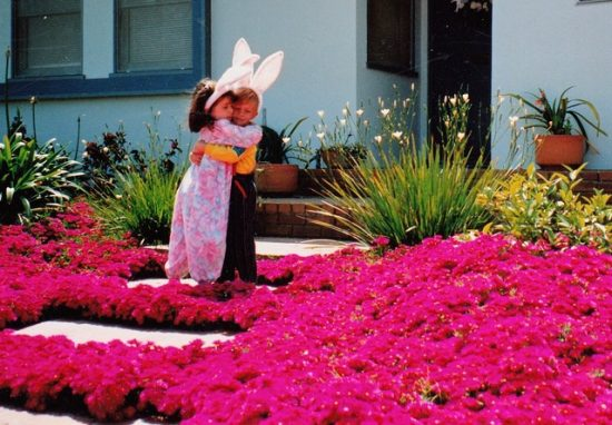 Two kids hugging in bunny ears in front of a light blue house amongst pink ice plant