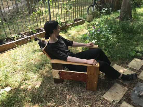 Woman sitting in Rietveld crate chair in garden with a cat behind her