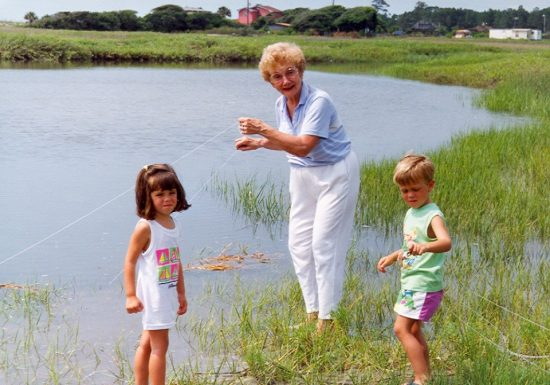 A grandmother in white trousers crabbing with her two four-year-old grandkids