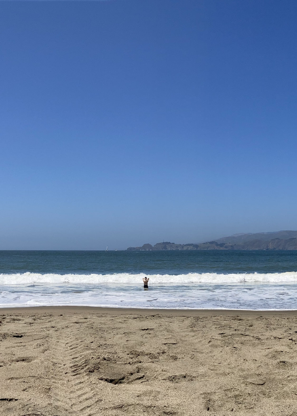 A distant woman standing in the surf at Baker Beach