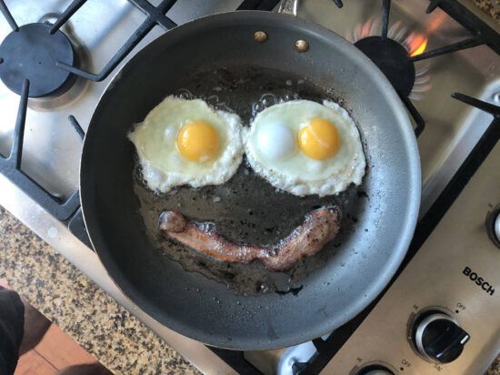 A bird's-eye view of eggs and bacon in a pan arranged like a smiley face