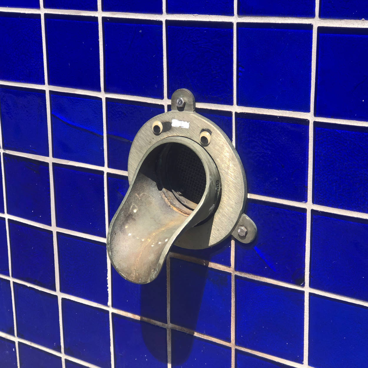 A condensation pipe outlet on a blue tile wall with googly eyes on it to make it look like a face
