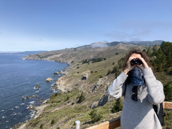 A woman looking at a camera with binoculars in front of the Northern California coastline