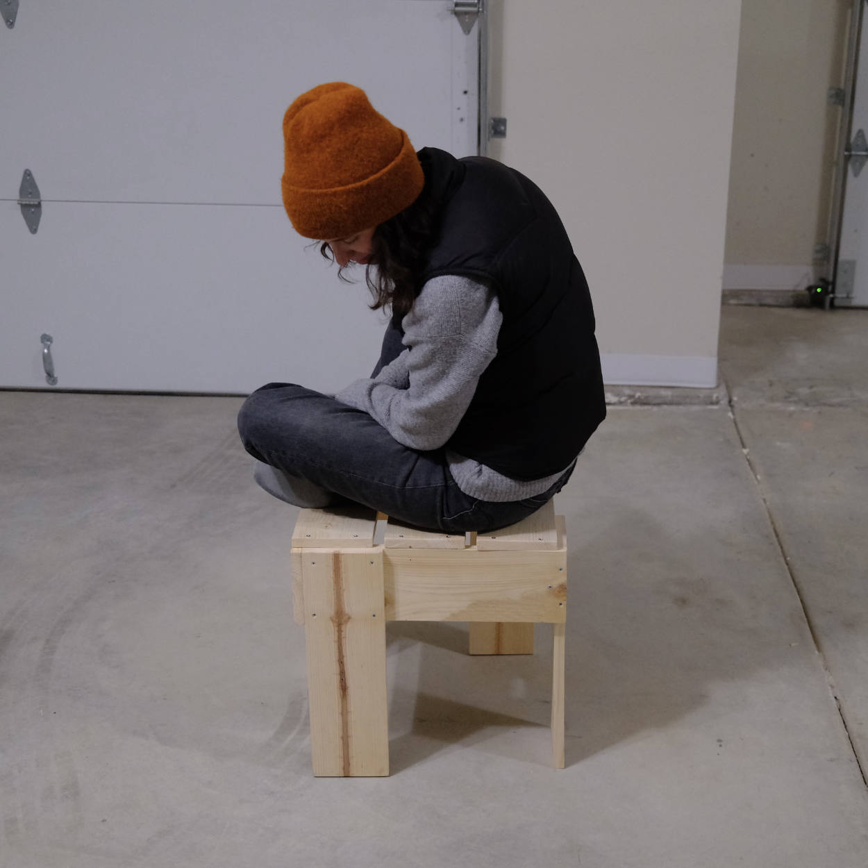 A woman in an orange beanie sitting on a pine stool made in Rietveld's crate style