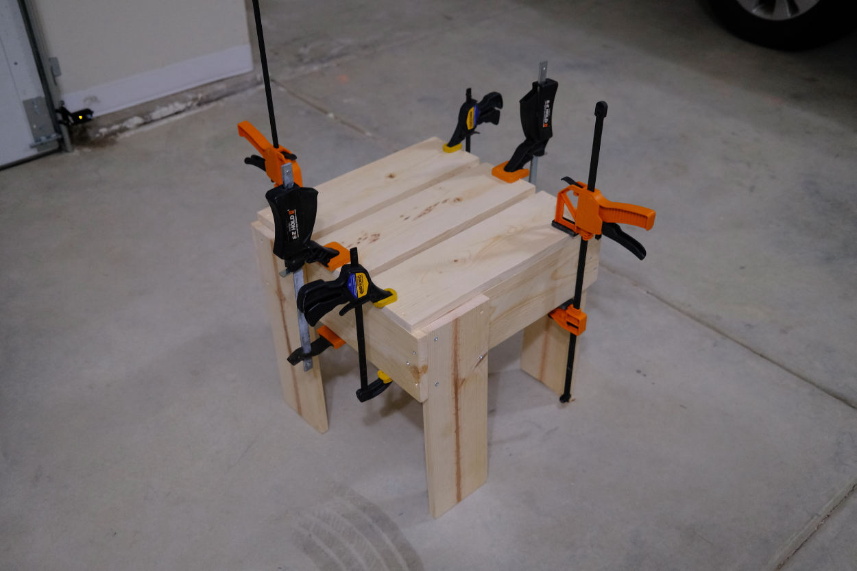 Seat slats clamped to the base of a Rietveld crate stool