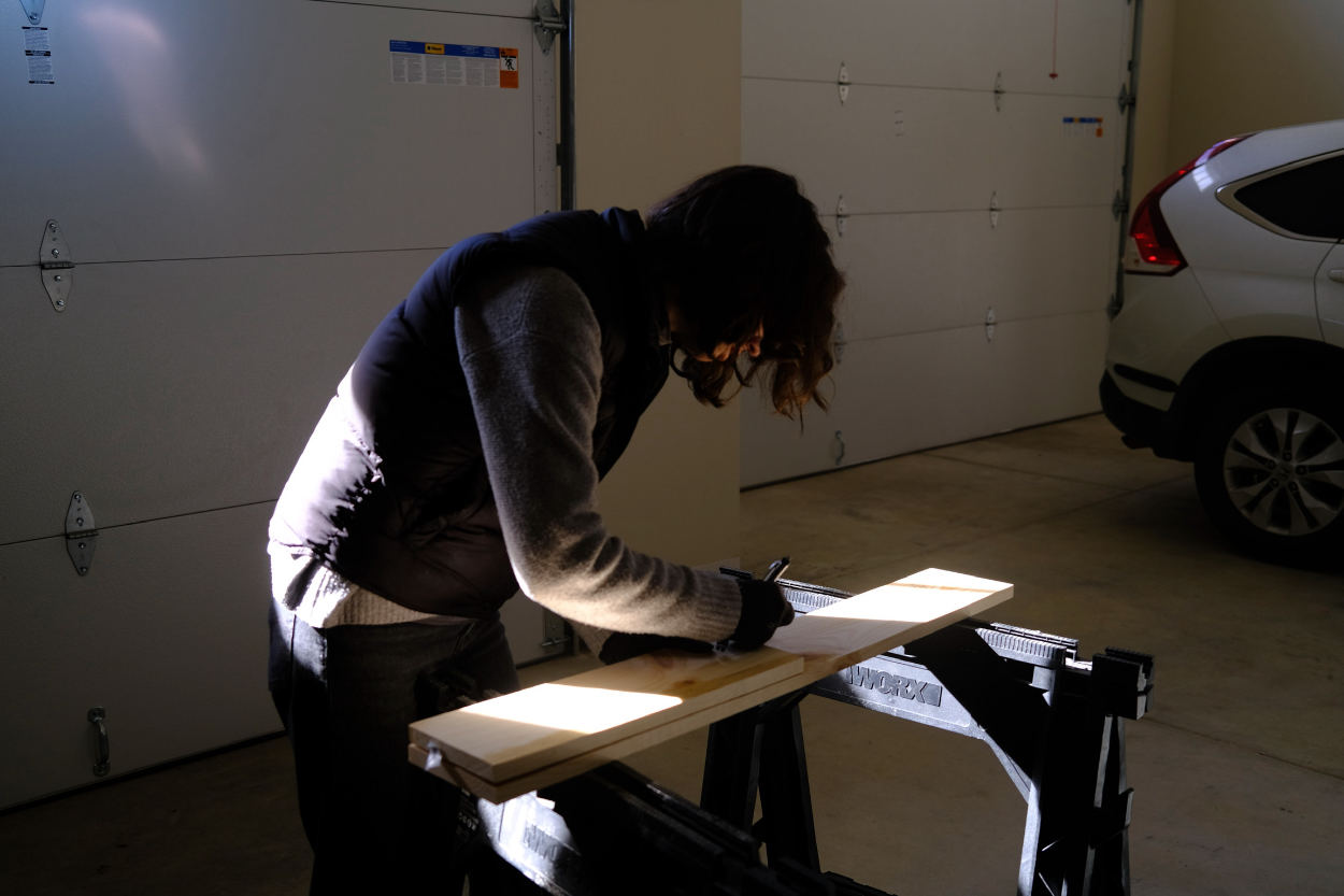 Woman working marking a plank of wood in a garage