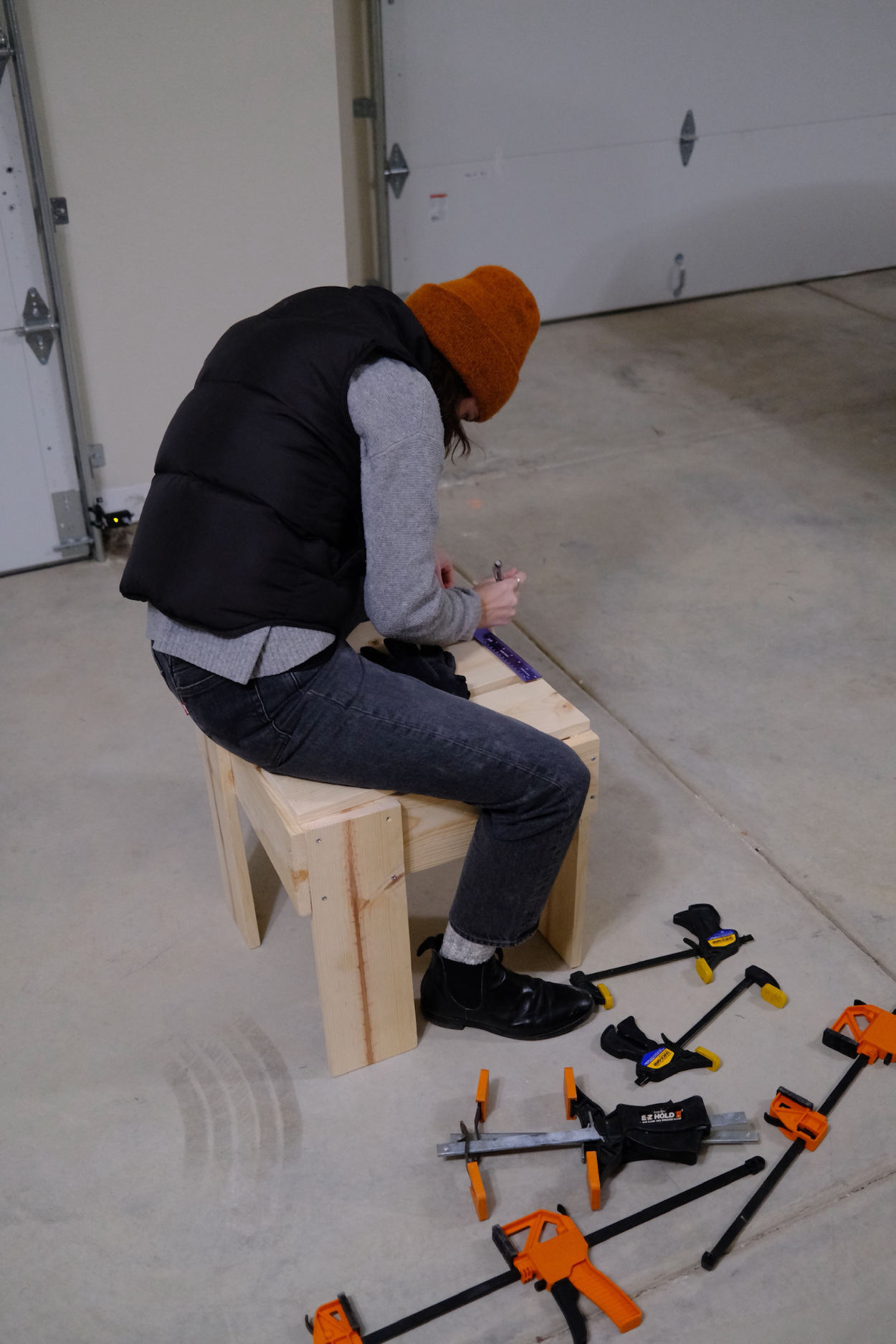 Woman marking pilot holes on the seat of a Rietveld crate stool